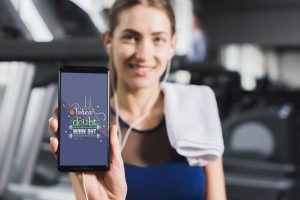 Woman holding a smartphone with motivation slogan to make a workout