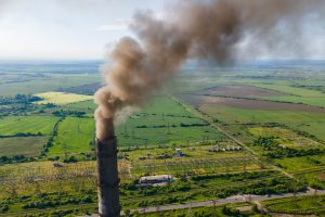 Aerial view of coal power plant high pipes with black smokestack polluting atmosphere and emitting a lot of CO2