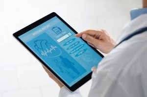 Doctor is holding digital tablet at hospital to review report. He is checking patient data on digital tablet using a EHR system.