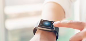 A hand is touching a smartwatch which is one of medical wearable devices