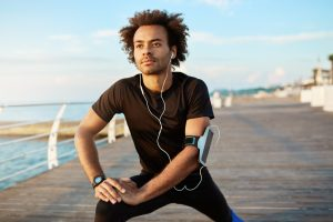 A male afro-american jogger that is stretching legs before running wears a smartphone attached to his arms with a fitness app