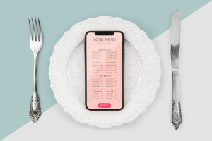 Diet & nutrition apps: How to create apps serving nutritional guidelines? Smartphone is laying on a white plate flanked by silver cutlery