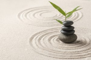 Mediation apps teach users how to meditate with a guided approach. Picture with stacked zen stones sand background art of balance concept