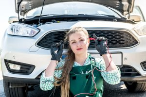 Maintenance of electric cars - woman mechanic searching problems with car engine