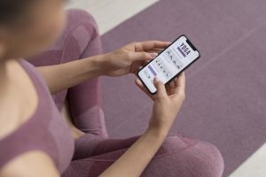 Fitness woman is doing yoga using mobile app